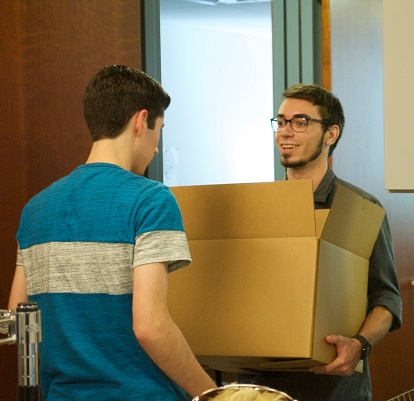 Steven and  Alex give each other hand with the heavy boxes (thank goodness for interns!)